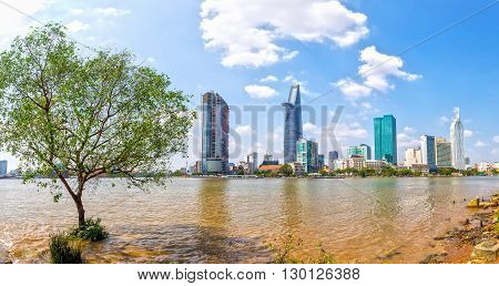 Ho Chi Minh City, Vietnam - January 19th, 2016: Panorama  skyscrapers riverside in sunny day, in front of the riparian cork trees toward the busy urban areas expressed economic development in the opening up Ho Chi Minh city, Vietnam