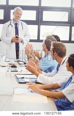 Doctors applauding a fellow doctor for his speech in conference room