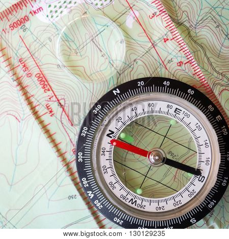 A compass, used for location,  placed on a map.