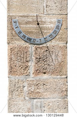 Old fashioned sun dial on a stone wall isolated on white.