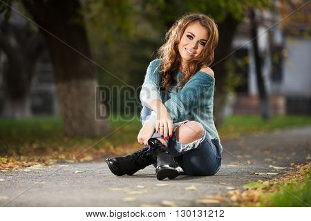 Young fashion woman with long curly hairs sitting on city street