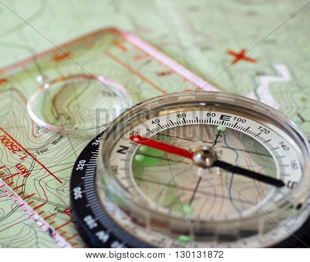 A compass placed on a map. X marks the spot.