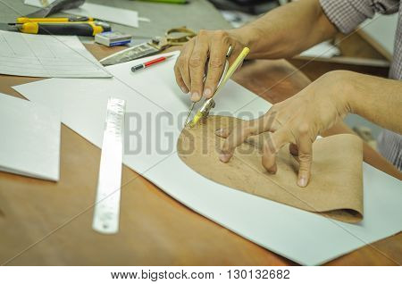 Young Man Measuring and Cutting Leather in Workshop. Leather worker or tailor cutting leather sheet with the help of measurement and cutting instruments. The image of working desk of the leather factory is in sharp focus and no human face is visible in th