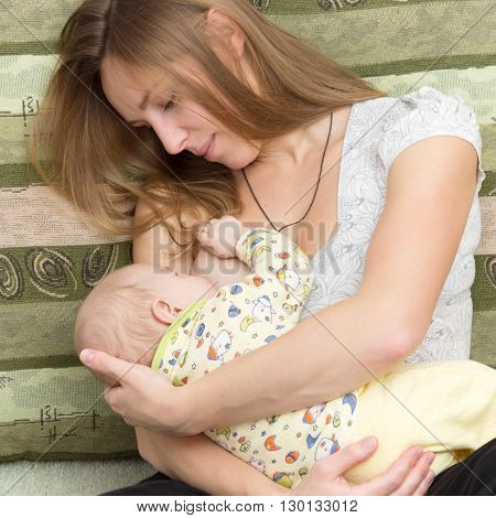 Portrait of young mother breast-feeding her breastfed child