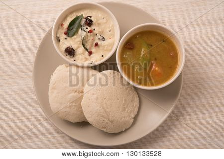 traditional south indian food idli or idly with sambar and white coconut coconut in white plate