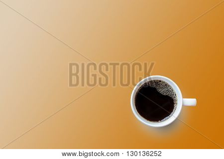 Black coffee cup on orange background. Top view