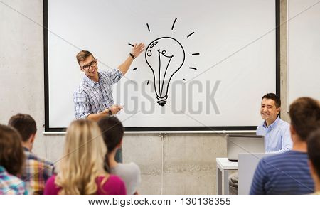 education, high school, idea and people concept - student standing with remote control in front of teacher and classmates in classroom and showing light bulb on white board in classroom