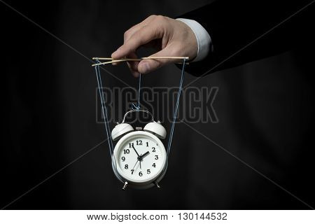 Hand of business man manages a clock hanging on cords and symbolizing the time on dark background