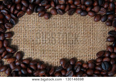 Dark roasted coffee beans on gunny sack texture with empty space on it