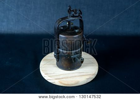 The old miner carbide lamp at a round wooden base