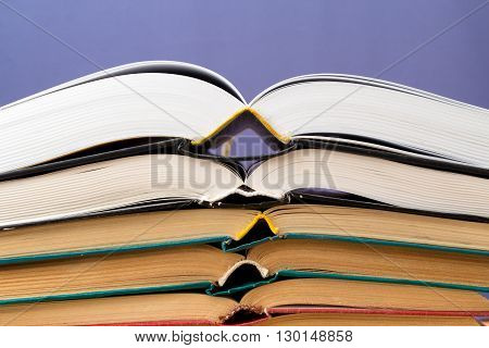 A lot of different books are opened and lie on top of each other on a blue background