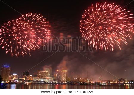 a burst of red fireworks explode above the mississippi river in new orleans during the annual fourth of july fireworks celebration. poster