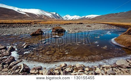 Snowy mountains reflected in lake. Severe mountains peaks covered by snow. Russia Siberia Altai mountains Chuya ridge.