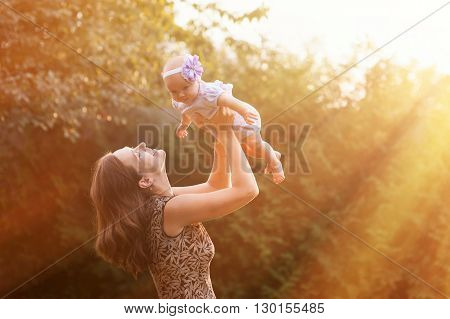 Young mother with child outside. young mother holding her daughter in her arms.