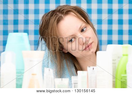 Girl is drying her hairs surrounded by various cosmetics in bathroom. Skincare and beauty concept. Frontal portrait