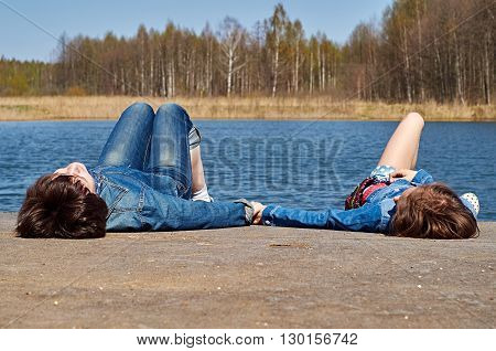 Mother and daughter lying on gangway near the lake enjoying warm spring weather