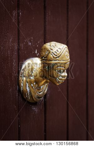 Antique door knocker in the shape of a human head on a wooden door in Venice Italy