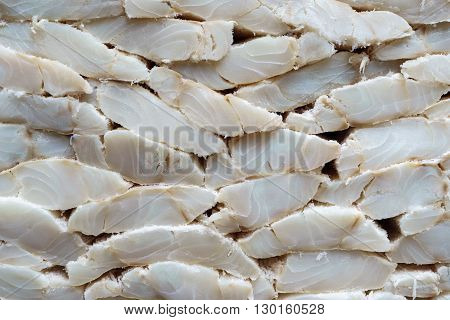 Photo of stand full of salty codfish fillet, side view