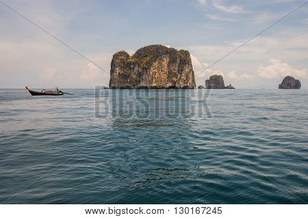Longtail boat with Poda island background at Krabi. Poda is famous island travel package tour by traditional longtail boat at Krabi Andaman ocean Thailand