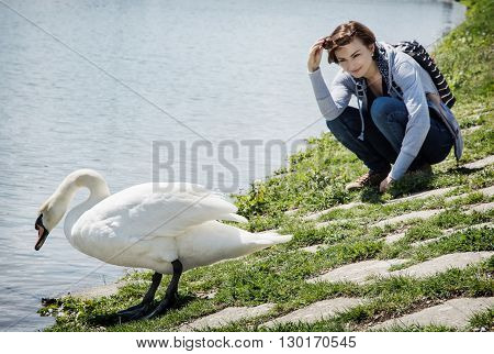 Young woman posing with white swan on the lakeside. Beauty and nature. Bird watching theme. Natural scene.