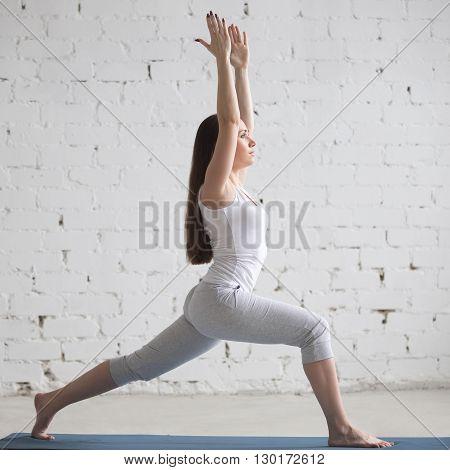 Profile Portrait Of Beautiful Woman Doing Virabhadrasana I Pose