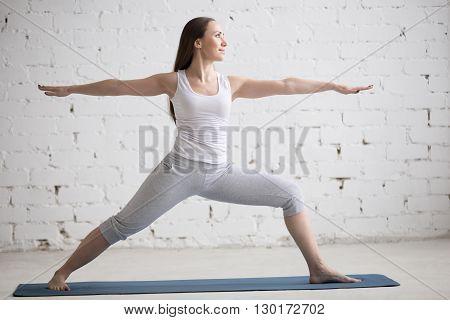 Side View Portrait Of Happy Woman Doing Warrior Ii Pose
