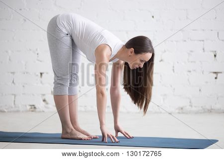 Attractive Fit Young Woman Doing Ardha Uttanasana Pose In White Loft
