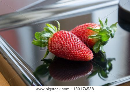 2 strawberries on a black background with reflection