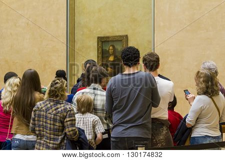 Paris, France - May 12: A crowd of people huddled next to a special painting