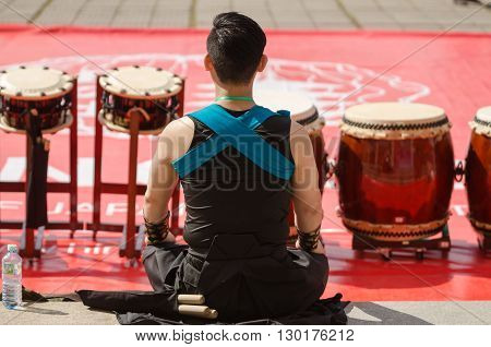 Japanese taiko artist sits on floor back to camera near  the drums
