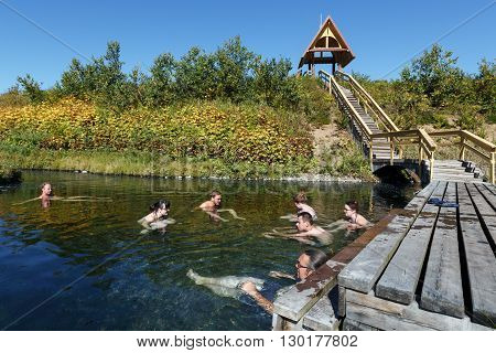 NALYCHEVO NATURE PARK, KAMCHATKA PENINSULA, RUSSIA - SEP 7, 2013: Group hot springs in Nalychevo Nature Park - tourists take a therapeutic (medicinal) baths in pool with natural thermal mineral water having balneological properties.