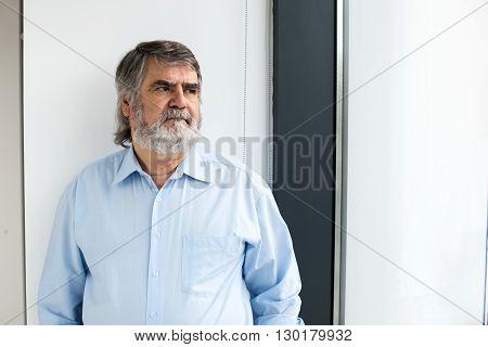 Teacher Standing Next To A Window