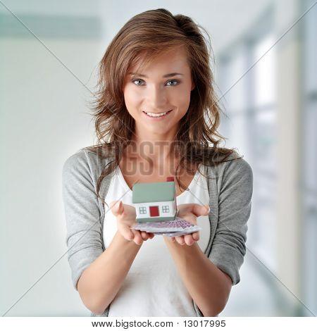 Mooie jonge vrouw houdt van euro rekeningen en huis model over Wit - onroerend goed lening concept