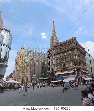VIENNA AUSTRIA - JULY 12; Stephansplatz square with St. Stephen cathedral and tourists walking around in Vienna Austria - July 12 2015: Famous historical landmark St. Stephen cathedral during sunny summer day with people walking around