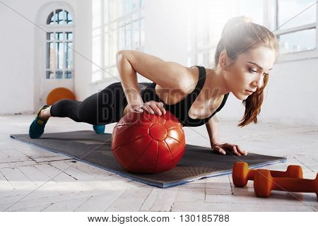 Beautiful young slim woman doing some gymnastics at the gym with medball