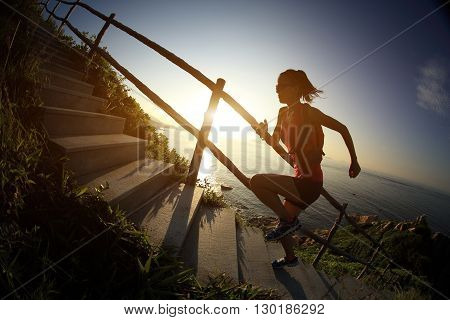 fitness woman trail runner running on seaside mountain stairs training for cross country running.