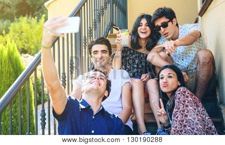 Closeup of young happy people taking a selfie with a smartphone outdoors sitting on the home stairs steps. Young people lifestyle concept.