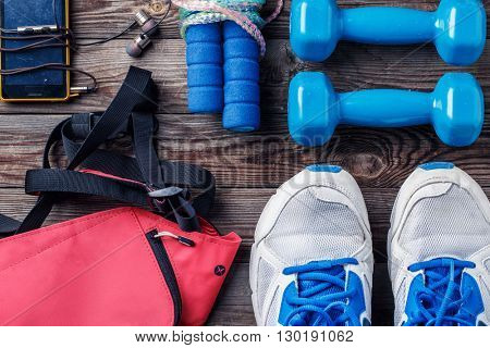 Shoes and sports equipment on wooden floor, top view