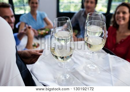 Waiter serving wine to groups friends sitting on table in restaurant