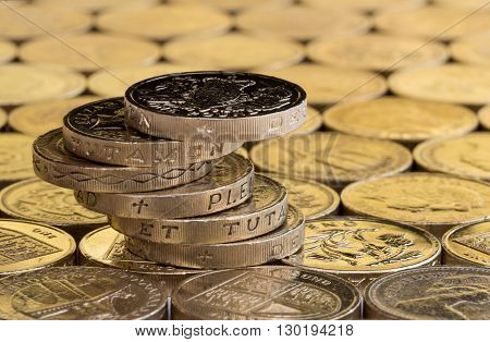 British money pound coins balanced in a precarious stack on a background of more money.