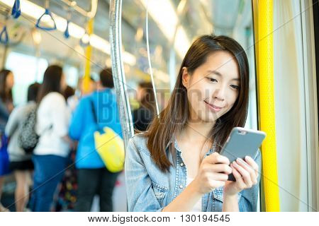 Woman use of mobile phone inside train compartment at Hong Kong