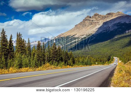 Highway in Banff National Park. Rocky Mountains. Mountains and colorful autumn forest illuminated by the sunset