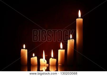 Set of lighting candles on nice dark background