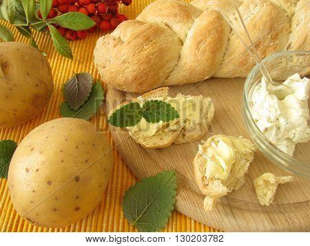 Homemade potato yeast plait and fresh potatoes