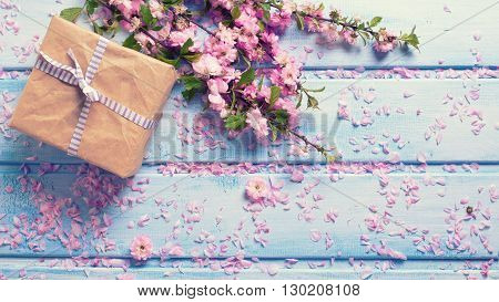 Wrapped box with present and sakura pink flowers on blue wooden planks. Selective focus. Place for text. Flat lay. Top view. Toned image.