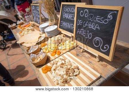 Several kinds of cheese served on vintage wooden table and blackboards written in spanish
