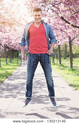 handsome man jumping on path lined with cherry blossom