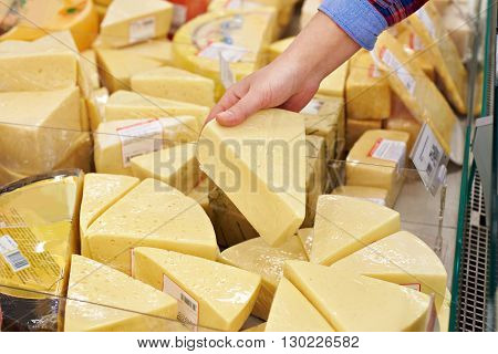 Hand With Piece Of Cheese In Store