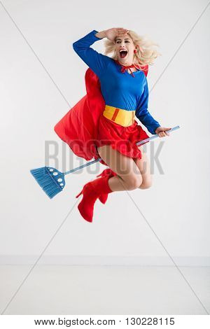 Cheerful excited superwoman flying on broom, isolated on white