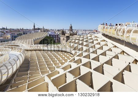 Seville, Spain - May 1, 2016: Seville cityscape as seen from Metropol Parasol building, a wooden structure at Plaza de la Encarnacion. People walking around and enjoying the view.